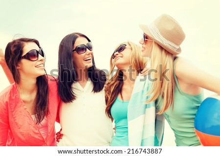 summer holidays, vacation and beach activities concept - smiling girls with ball and towel on the beach - stock photo