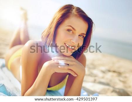summer holidays, vacation and beach concept - girl sunbathing on the beach - stock photo