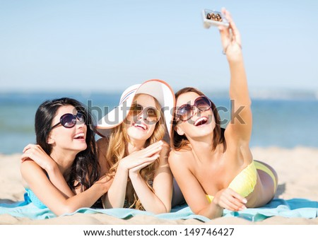 summer holidays, vacation and beach concept - girls in bikinis taking selfie on the beach - stock photo