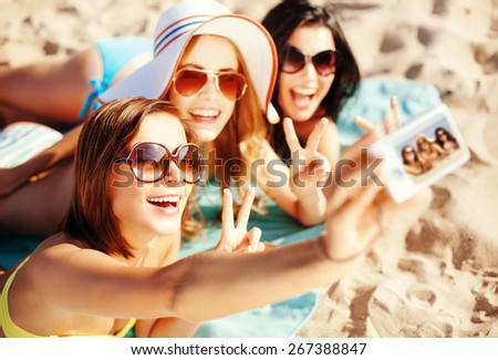 summer holidays, vacation and beach concept - girls taking self photo on the beach - stock photo