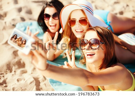 summer holidays, vacation and beach concept - girls taking selfie on the beach - stock photo