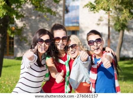 summer holidays, vacation and people concept - happy teenage girls in sunglasses or young students showing thumbs up over campus background - stock photo