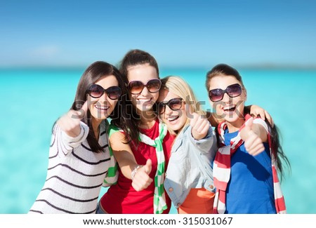 summer holidays, vacation and people concept - happy teenage girls in sunglasses or young women showing thumbs up over beach background - stock photo