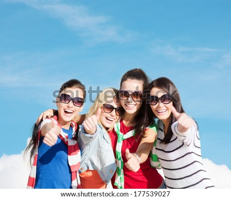 summer, holidays, vacation, happy people concept - beautiful teenage girls or young women showing thumbs up - stock photo