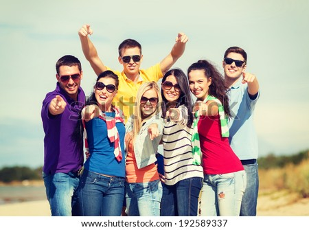 summer, holidays, vacation, happy people concept - group of friends having fun on the beach and pointing at you - stock photo