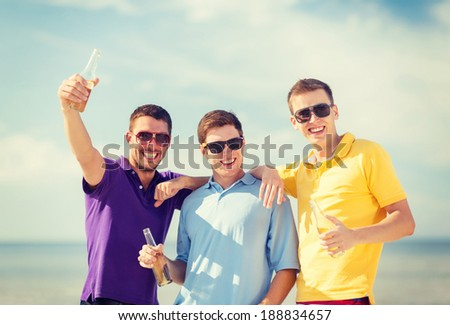 summer, holidays, vacation, happy people concept - group of friends having fun on the beach with bottles of beer or non-alcoholic drinks - stock photo