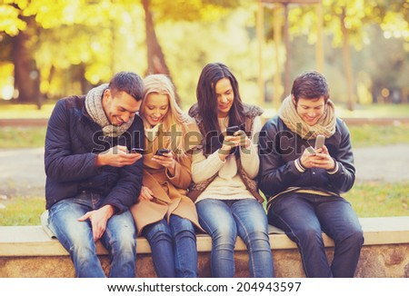 summer, holidays, vacation, happy people concept - group of friends or couples with smartphones having fun in autumn park - stock photo