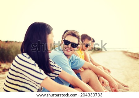 summer, holidays, vacation, happy people concept - group of friends or volleyball team having fun on the beach - stock photo