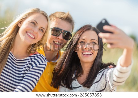 summer holidays, vacation, happy people concept - group of friends taking selfie with cell phone on the beach - stock photo