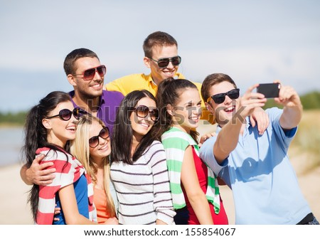 summer, holidays, vacation, happy people concept - group of friends taking selfie with smartphone - stock photo