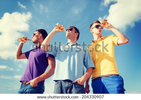 summer, holidays, vacation, happy people concept - group of male friends having fun on beach with bottles of beer or non-alcoholic drinks - stock photo