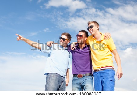 summer, holidays, vacation, happy people concept - group of male friends walking on the beach pointing finger somewhere - stock photo