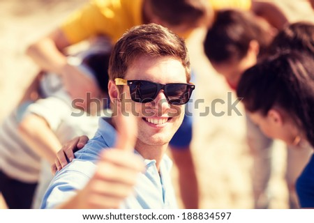 summer, holidays, vacation, happy people concept - man with group of friends on the beach showing thumbs up - stock photo