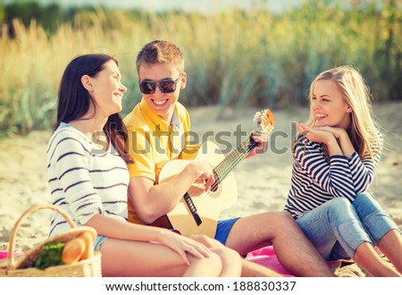 summer, holidays, vacation, music, happy people concept - group of friends with guitar having fun on the beach - stock photo