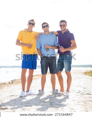 summer holidays, vacation, people and bachelor party concept - group of happy male friends drinking beer and walking along beach - stock photo