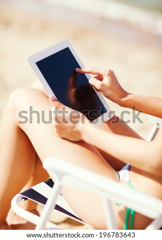 summer holidays, vacation, technology and internet - girl looking at tablet pc on the beach chair - stock photo