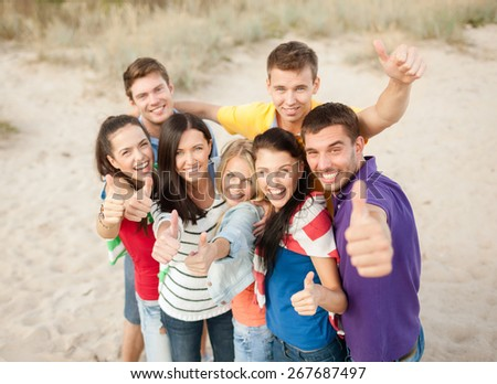 summer holidays, vacation, tourism, travel and people concept - group of happy friends having fun and showing thumbs up on beach - stock photo
