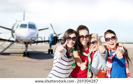 summer holidays, vacation, travel and people concept - happy teenage girls in sunglasses or young students showing thumbs up over airport background - stock photo