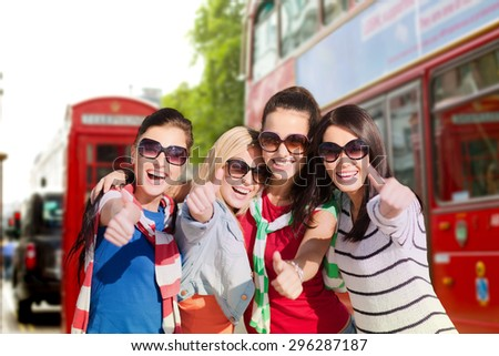 summer holidays, vacation, travel, friendship and people concept - happy teenage girls or young women in sunglasses showing thumbs up and laughing over london city street background - stock photo