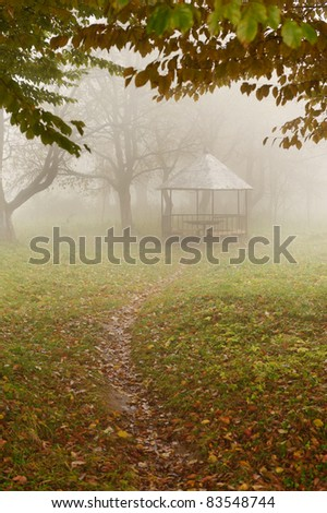 summer house in foggy forest. Autumn weather - stock photo