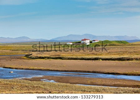 Summer Iceland Landscape with River, Mountains and White Farmhouse - stock photo