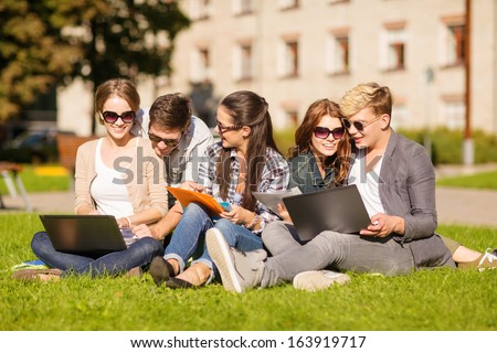 summer, internet, education, campus and teenage concept - group of students or teenagers with laptop, notebooks, files and folders - stock photo