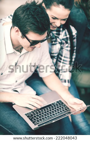 summer, internet, education, campus and teenage concept - students or teenagers with laptop computer hanging out - stock photo