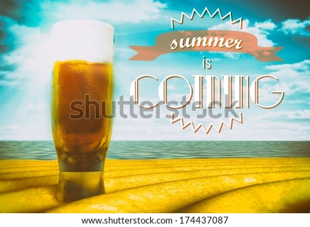 Summer is coming sign with beer glass on beach - stock photo