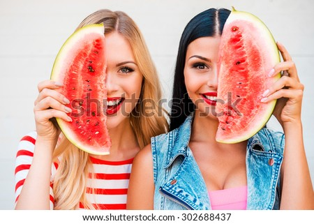 Summer is time for fun. Two playful young women holding slices of watermelon against half part of their face and smiling while standing outdoors - stock photo