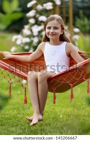 Summer joy, hammock - lovely girl in a hammock, rest in the garden concept - stock photo
