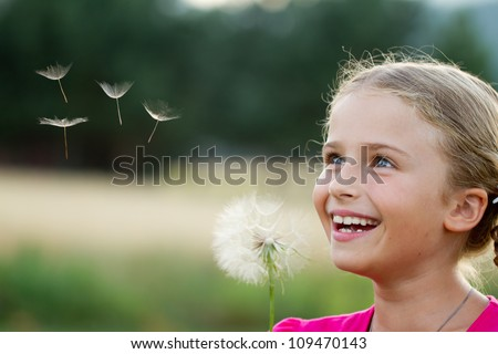 Summer joy - lovely girl blowing dandelion - stock photo