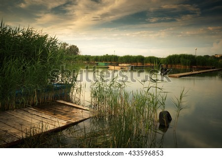 Summer lake pier reed landscape boat - stock photo