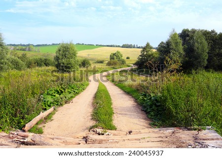 summer landscape dirt road among meadows and forests on a cloudy day - stock photo