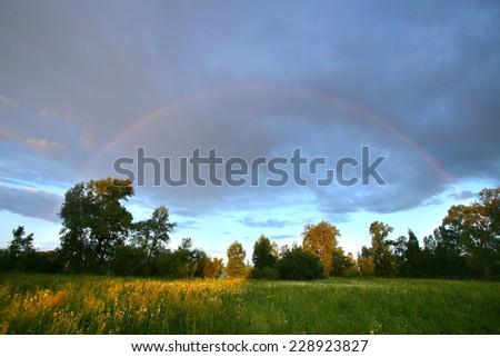 summer landscape dramatic clouds over the meadow at sunset and a rainbow after the rain - stock photo