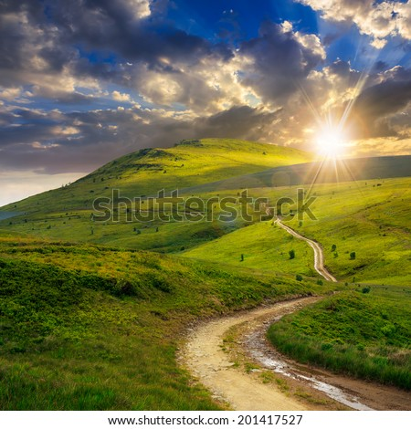 summer landscape. mountain path through the field turns uphill to the sky at sunset - stock photo