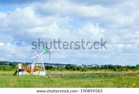 summer landscape oil pump in a green field, cloudy sky above him and the forest on the horizon - stock photo