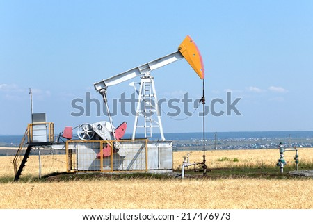 summer landscape oil pumps in the grain fields on the background of the blue sky on a sunny day - stock photo