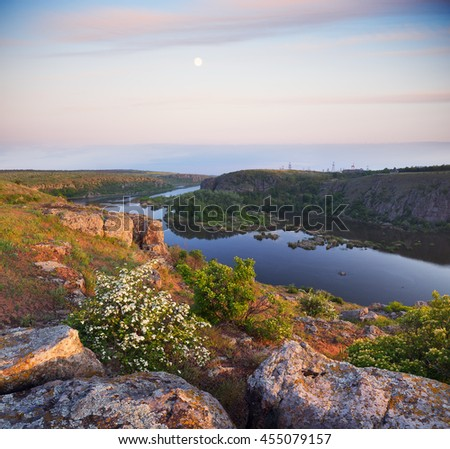 Summer landscape on a sunny morning. Canyon and river. Blossoming hawthorn bush and large stones - stock photo