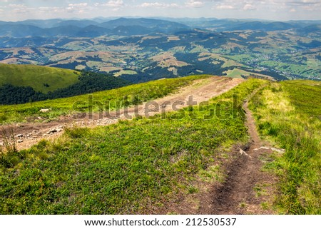 summer landscape. path goes from the mountain range down to village in valley at the mountain foot - stock photo