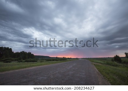 summer landscape road sunset dramatic clouds on blue sky and green meadows - stock photo