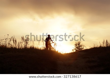 summer landscape silhouette of a boy on a bicycle, with rolling hills on the background of golden sunset - stock photo
