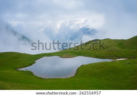 Summer landscape with a mountain lake. Cloudy day. Lake koruldi, Main Caucasian ridge. Zemo Svaneti, Georgia  - stock photo