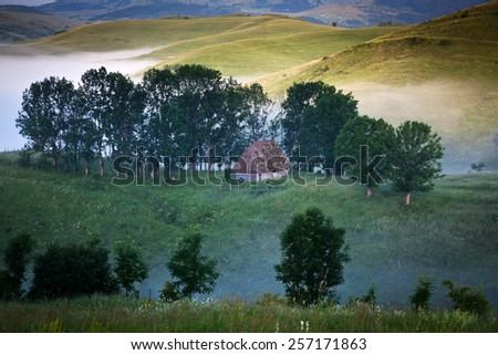 Summer landscape with a mountain village in the mist - stock photo