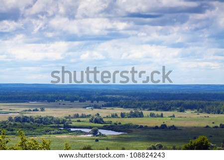 Summer landscape with green meadow under cloudy sky - stock photo