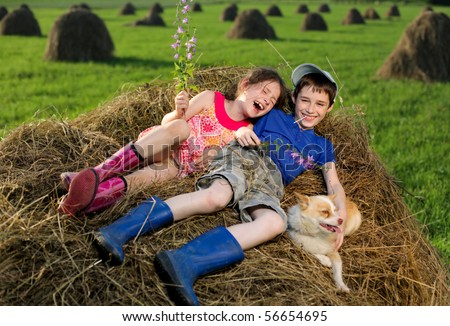 Summer landscape with hay cocks, couple children sitting on large hay - stock photo