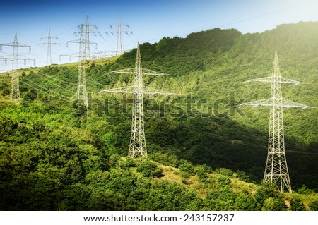 Summer landscape with high voltage transmission towers - stock photo