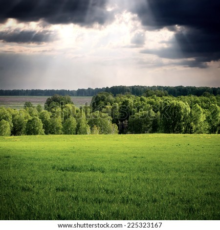 Summer Landscape with the Green Field and Dramatic Cloudscape - stock photo