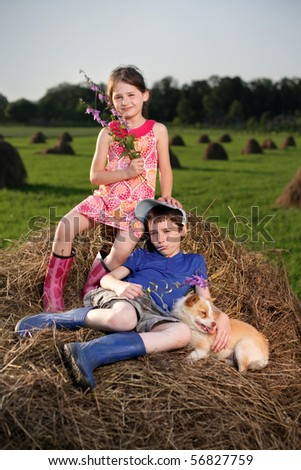 Summer lanscape with hay cocks, couple children sitting on large hay - stock photo