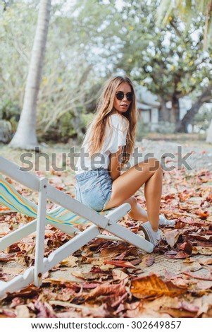 Summer lifestyle portrait girls going crazy, screaming, laughing having fun on tropical island,sitting and chilling at hammock. wearing white tops and sunglasses,ready for party, joy,fun. - stock photo