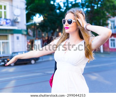 Summer lifestyle portrait of pretty young hipster traveler girl, walking alone in city center of Europe, trying to catch taxi to airport terminal or railway station. Young woman hitchhiking  - stock photo